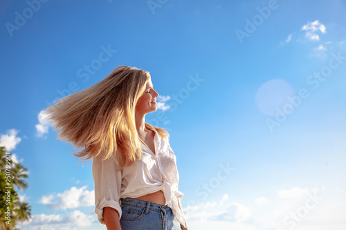 Valokuvatapetti Beautiful young blonde girl with flowing hair and dimples against the blue sky a