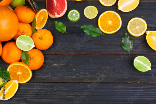 Fotografie, Obraz  Bright composition of citrus fruits on black wooden background