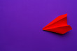 white paper airplane on a purple background