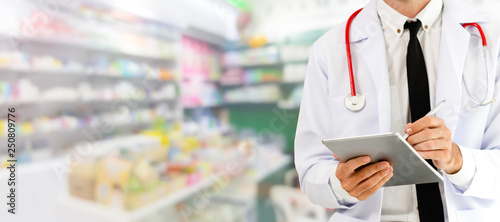 Fotografia  Pharmacist using tablet computer at pharmacy.