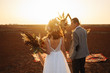 canvas print picture - young and beautiful bride and groom enjoy each other. Wedding day in boho style. Sunshine portrait of happy bride and groom outdoor in nature at sunset. Warm summertime.