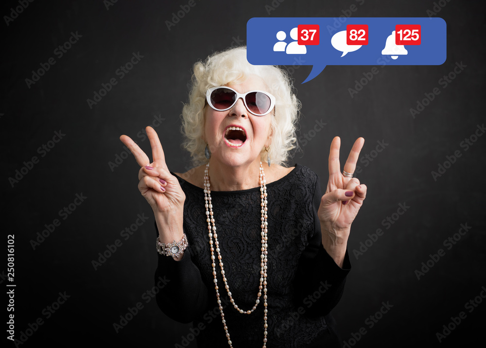 Fototapeta Old woman still rocking and being active on social media