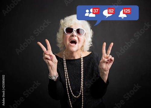 Obraz Old woman still rocking and being active on social media - fototapety do salonu