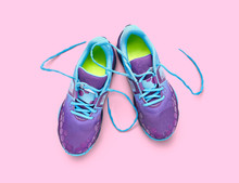 Top View Of Blue And Purple Trainers Isolated On A Pink Background.