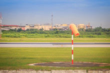 Orange Windsock Or Wind Vane In Moderate Wind On Red White Pole Against Clear Blue Sky On Sunny Day At Aviation Area. Wind Vane Direction Sign At The Airport Field.