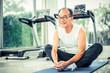 Senior man do body stretching in fitness center.