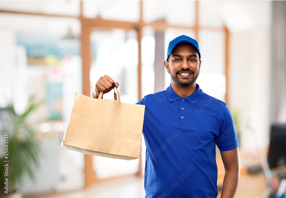 Fototapety, obrazy: takeaway service and people concept - happy indian delivery man food in paper bag in blue uniform over office background