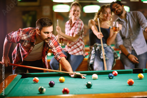 Foto Young handsome man playing billiard game.