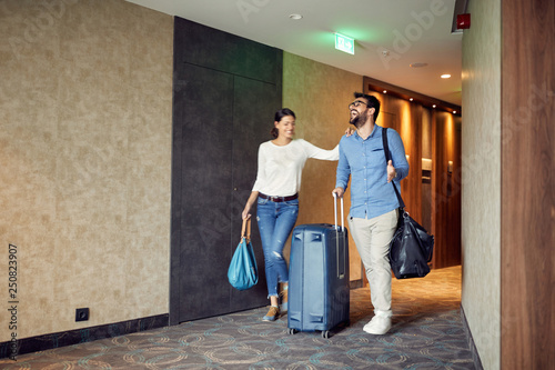 Stampa su Tela Man and woman arriving at hotel lobby with suitcase at vacation.