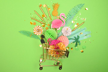 Attributes of the holiday, gifts and confetti in a basket for a supermarket on a plain background. The concept of holiday shopping. Flat lay, top view