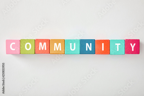 Fotografia, Obraz  top view of community lettering made of multicolored cubes on grey background