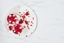 Fresh Pomegranate Juice With Ice And Red Pomegranate Seeds On White Marble Serving Plate Over Marble Background. Top View With Copy Space For Text. Overhead Shot.