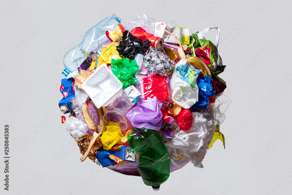 Fototapeta A globe of the earth with trash over white background, the concept of ecology problem and World Environment Day. Photo with message for social advertising, place for inscription