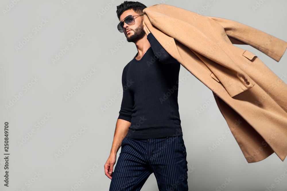Fototapeta Elegant young handsome main coat wearing glasses. Studio fashion portrait.