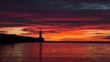 A Beautiful Sunrise Over The North Pier Lighthouse At The Mouth Of The River Tyne In Tynemouth, England
