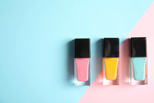 Bottles Of Nail Polish On Color Background, Top View With Space For Text