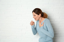Woman Suffering From Cough Near Brick Wall. Space For Text