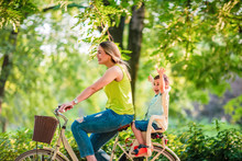 Happy Family. Mother And Son Riding A Bicycle Together Outdoors In A City Park.