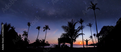Foto auf Leinwand Schwarz Panoramic landscape of man standing on the coconut beach with a million stars