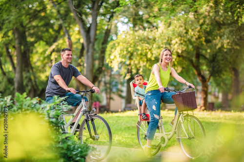 Obraz Happy family. Smiling father and mother with kid on bicycles having fun in park.. - fototapety do salonu