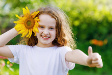 Laughing Child With Sunflower, Showing Thumbs Up.