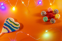 Candies And Colorful Candies On An Orange Background. Small Led Lights Of Colors. Horizontal View Birthday Celebration Concept. Invitation Card.