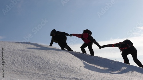 Photo climbers hand in hand climb to top of a snowy mountain