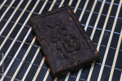 Fotografie, Obraz  Pressed tea brick with Chinese hieroglyphs. Press tea texture.