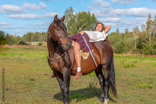 Fototapeta Girl in a Scottish kilt on a horse, holding a sword in her hand obraz