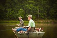 Mature Men Fishing On Boat In Lake