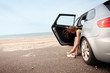 Woman tying shoe sitting in car