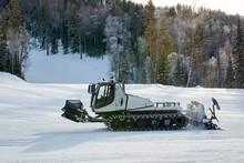 Snowcat On The Mountains And Forest Frosty Winter Day. Snowcat Is Equal To Snow On A Ski Slope In A Ski Resort.