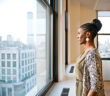 Side View Of Businesswoman Looking Through Window In Office