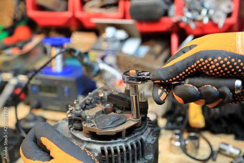 Fototapeta Dokręcanie regulatora napięcia w alternatorze samochodowym. obraz