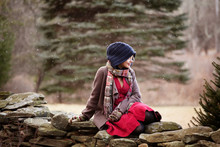 Woman In Warm Clothing Sitting On Stone Wall During Snowfall
