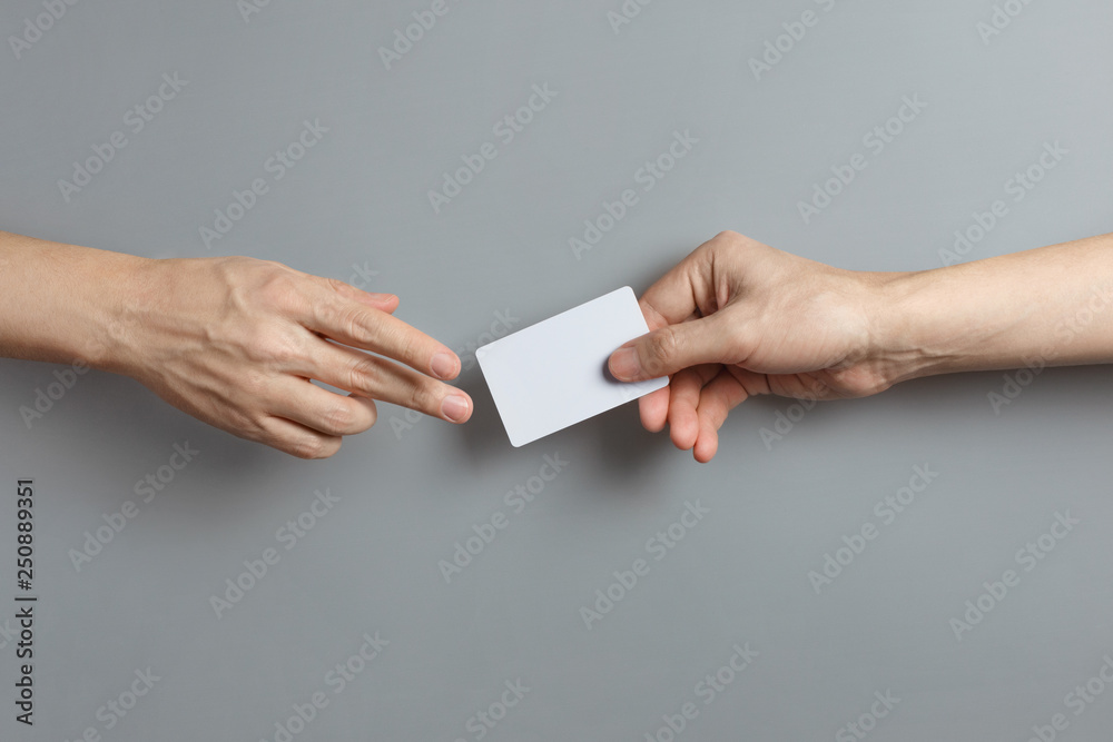 Fototapeta Hands sharing a blank card or a ticket/flyer on gray background