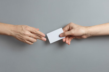 Hands sharing a blank card or a ticket/flyer on gray background