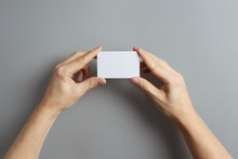 Hands Holding A Blank Card Or A Ticket/flyer On Gray Background
