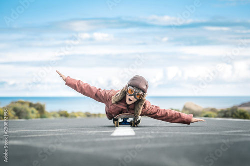 Fotografiet  Beautiful child lying skateboard flies vintage pilot suit with hat leather jacket and mask takes off from road central line with sea horizon smiles amused landing taxiing departure arrival