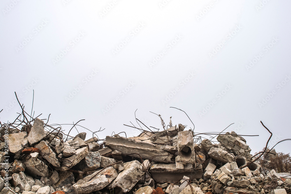 Fototapeta The rebar sticking up from piles of brick rubble, stone and concrete rubble against the sky in a haze.