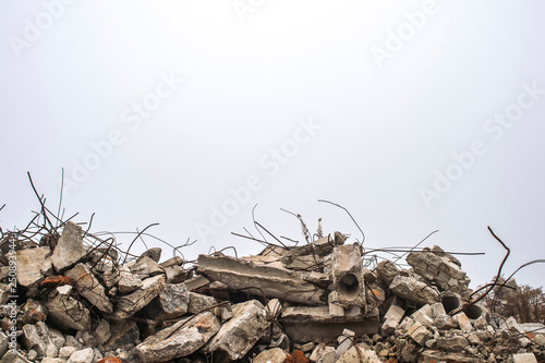 Fotografía  The rebar sticking up from piles of brick rubble, stone and concrete rubble against the sky in a haze