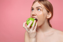 Portrait Of A Happy Beautiful Woman Holding An Apple Trying To Bite Him, With Healthy Teeth On A Pink Background