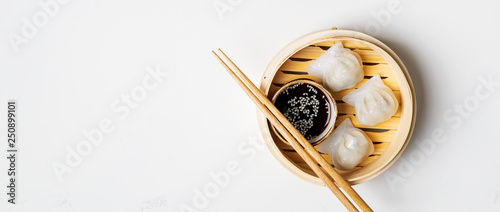 Photo  Traditional chinese steamed dumplings Dim Sums in bamboo steamer with sauces and chopsticks on light surface with copy space