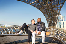 Two Men Embracing On Boardwalk Bench