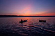 Silhouette Of Person In Canoe At Sunset