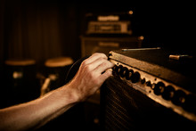 Hand Turning Dials On Guitar Amplifier
