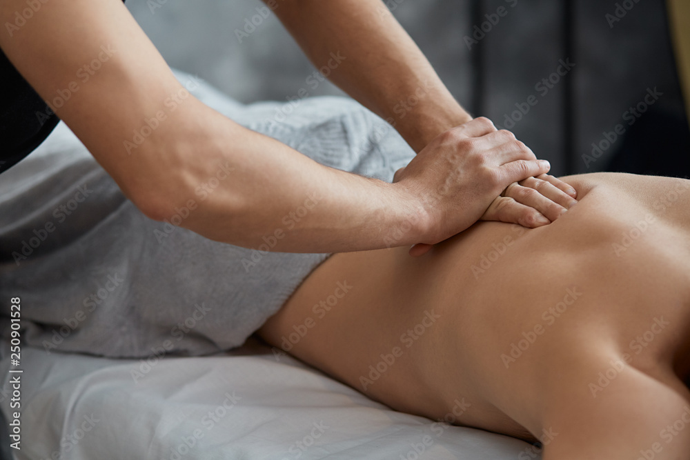 Fototapeta Young handsome man enjoying a back massage. Professional massage therapist is treating a male patient in apartment. Relaxation, beauty, body and face treatment concept. Home massage.