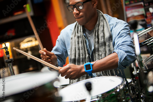 In de dag Muziekwinkel Man wearing glasses playing drums in music store