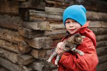Portrait Of Boy Wearing Knit Hat Holding Kitten