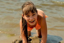 Teenage Girl Lying On The Sandy Beach On A Hot Summer Day